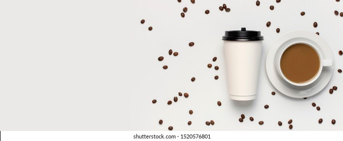 Coffee or tea paper cup, white cup with coffee, coffee beans on light gray background top view flat lay copy space. Take away coffee cup, mockup. Minimal composition, layout for design