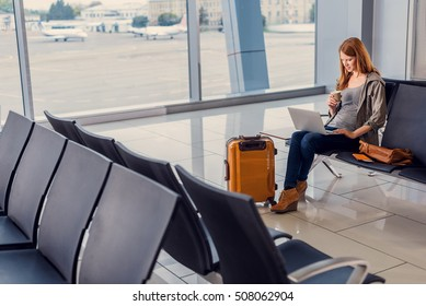 Coffee time. Attractive woman sitting in airport lounge, drinking coffee and working on laptop