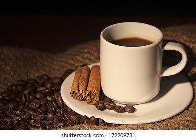 Coffee time: a coffee cup with coffee beans and cinnamon