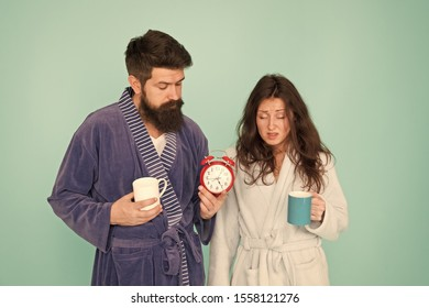 Its coffee time. Every morning begins with coffee. Couple in bathrobes with mugs. Man with beard and sleepy woman enjoy morning coffee or tea. Guy in bath clothes hold tea coffee. Breakfast concept.