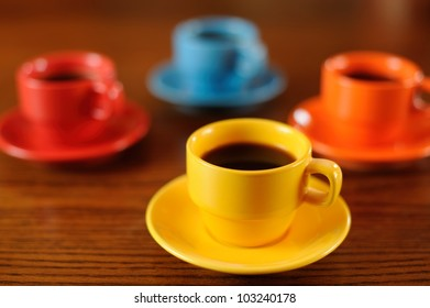 Coffee Time for Four. Group of four brightly-colored demitasse coffee cups on a wooden table. Shallow DOF.