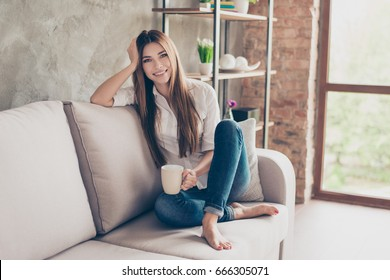 Coffee time. Smiling happy charming young lady on the couch at home having coffee and relaxing, so cozy and comfortable