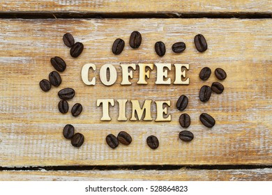 Coffee time written with wooden letters on rustic surface and coffee beans