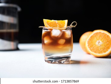 Coffee Tonic is the New Iced Coffee. New, cool handmade drink with coffee, tonic and ice cube. Decorated with an orange slice. Iced, caffeine cocktail