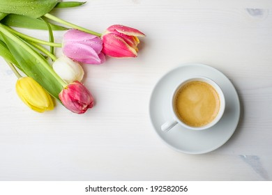 Coffee and tulips on a white wood table with some water on the tulips