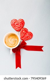 Coffee for Valentine`s day morning in white cup with two red heart lollipops and red ribbon bow on grey or blue background, copy space top view, creamy froth