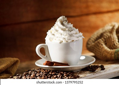 Coffee with whipped cream on wooden background