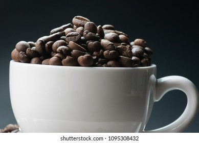 coffee in white cup and coffee beans are the background.