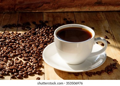 coffee in white cup and coffee beans on older wood background with ligh from windows