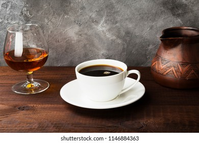Coffee in white cup with cognac and clay cezve on wooden background