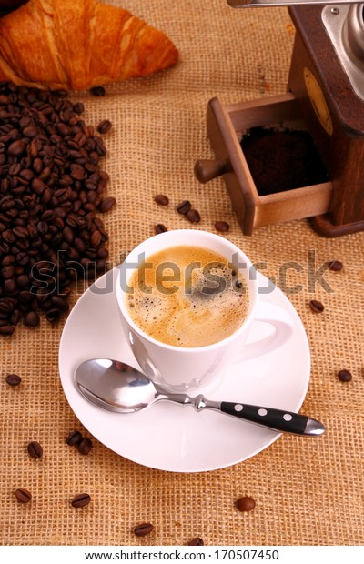 Coffee in white cup, croissant and coffee mill, top view