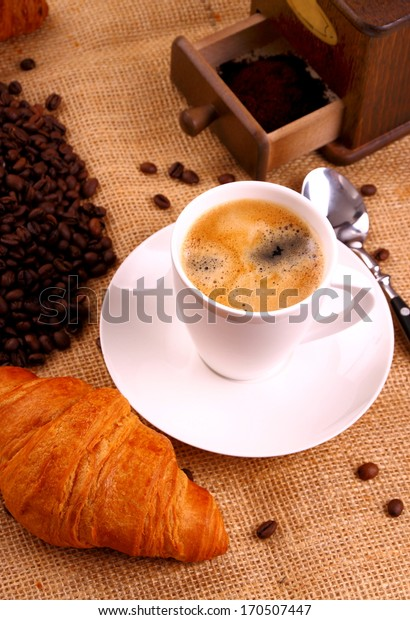 Coffee in white cup and croissant, top view
