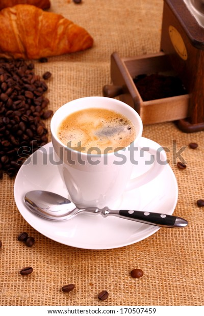 Coffee in white cup and croissant, vertical