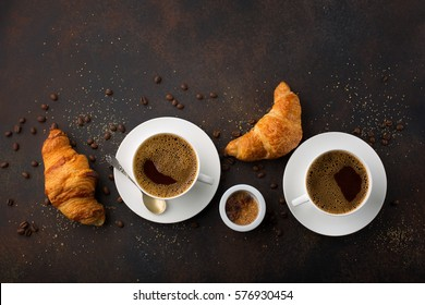 Coffee white cup, croissants on dark retro background, top view. Breakfast concept