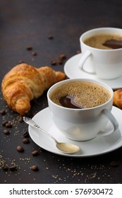 Coffee white cup, croissants on dark retro background, selective focus. Breakfast concept