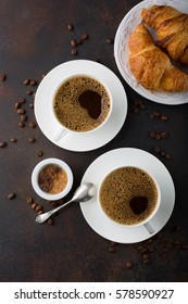 Coffee in white cup, croissants on dark retro background, top view. Breakfast concept