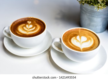 Coffee, white cup, heart shape and floral pattern on the white table in the morning coffee shop