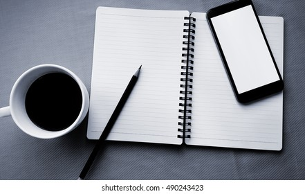Coffee in white cup with Journal book and smart phone