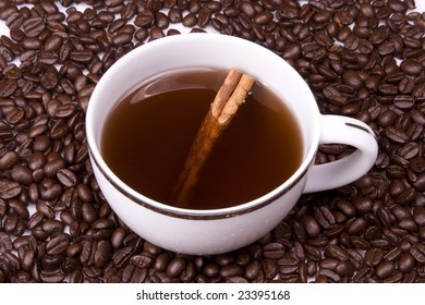 Coffee in white cup on coffee beans with a cinnamon stick