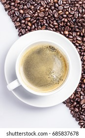 Coffee in a white cup on coffe beans and white background