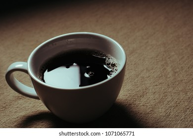 Coffee in a white coffee cup on an empty table.