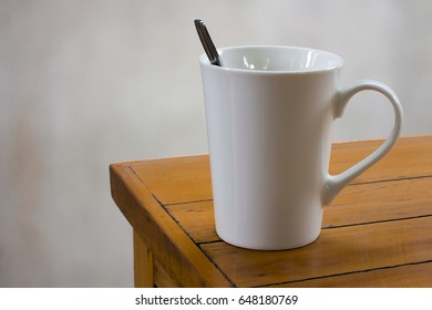 Coffee in white cup on wooden table