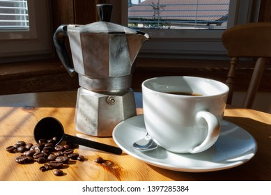 Coffee in a white cup and saucer with silver spoon, a tin of cof