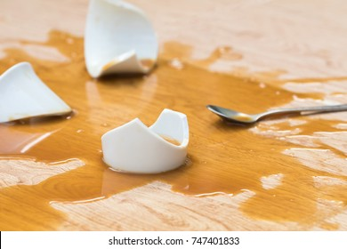 Coffee in white cup spilled with broken on wooden background texture