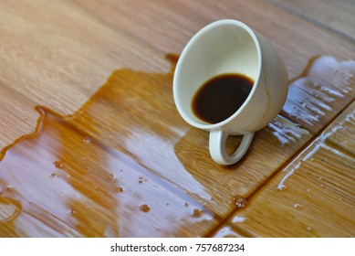 Coffee in white cup spilled on wooden floor