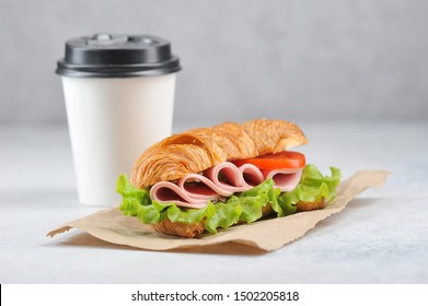 Coffee in a white paper cup and a ham sandwich. Coffee to go concept. Light background. Close-up. Negative space.