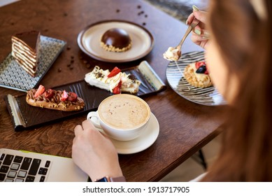 coffee in women's hands, sweet desserts on a wooden table