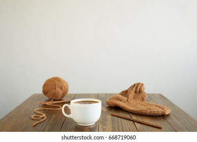 Coffee, woolen sock and knitting on a table