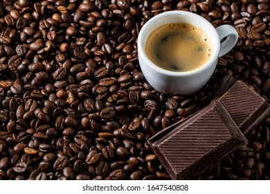 Coffeebeans with a cup of espresso and chocolate Pieces close up