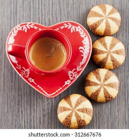 Coffeee in red cup and biscuits over wooden table, square image