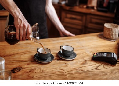 a coffeemaker is pouring beverage into the cups