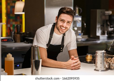 Coffeemaker. Professional Barista In Uniform Smiling Posing Standing At Bar Counter In Coffee Shop.
