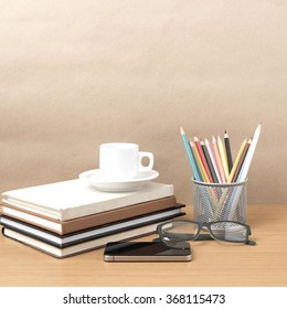 coffee,phone,eyeglasses,stack of book and color pencil on wood table background