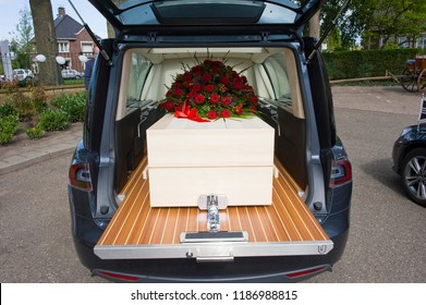 A coffin with a flower arrangement in a funeral car