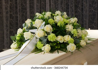 A coffin with a flower arrangement in a morgue