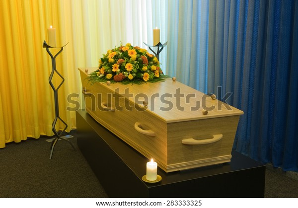 A coffin with a flower arrangement in a morgue with two burning candles