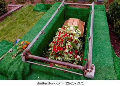 coffin with a lot of flowers in grave while funeral