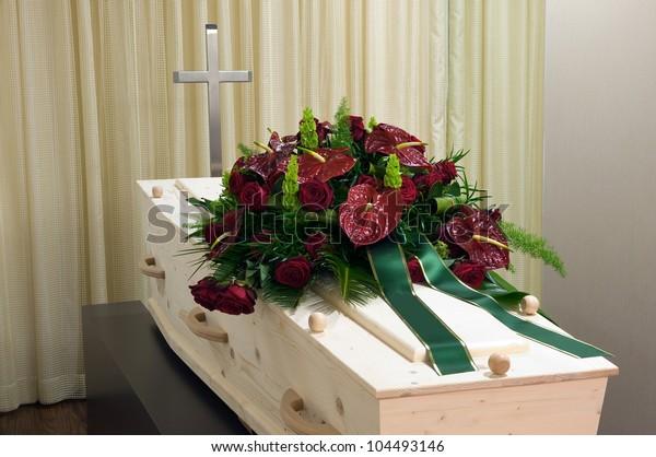 Ein Sarg in der Leichenhalle mit Kreuz und Blumenarrangements