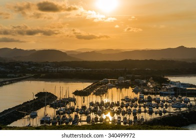Coffs Harbour bay with yachts, boats at sunset with sun reflection on the water