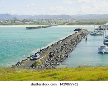Coffs Harbour Marina rock breakwall and the nearby restored Coffs Harbour ocean timber jetty. Safe haven for sailing and cruising vessels. New South Wales, Australia.