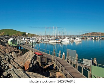 Coffs Harbour Marina. Waterfront walkway with boats in tropical water with blue sky backdrop. Safe haven for sailing and cruising vessels. New South Wales,  Australia.