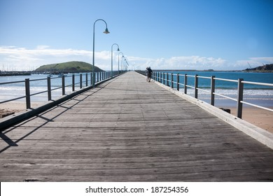 COFFS HARBOUR, NEW SOUTH WALES, AUSTRALIA - MARCH 22; distant figures of people walking out on the pier on March 22, 2014 in Coffs harbour, Australia.