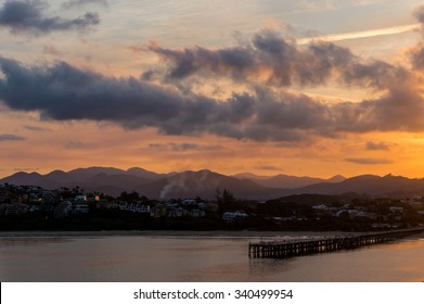 Coffs Harbour pier and town at dusk in winter with smoke coming out of chimneys
