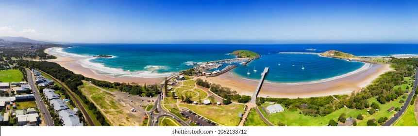 Coffs harbour regional town on NSW North coast in elevated aerial view - wide panorama of town's beach, marina, harbour and muttonbird island.