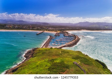 Coffs harbour town waterfront from Muttonbird island connected to shore by stone wave breaking wall protectin marina and local sandy beach.
