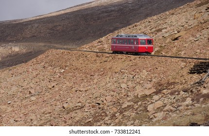 A cog railway train traveling on the side of the rocky mountain up to Pikes Peak, Colorado.